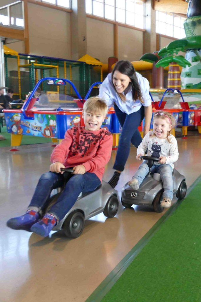 Kinder mit Ihrer Mutter auf Bobbycars im Sonnenlandpark