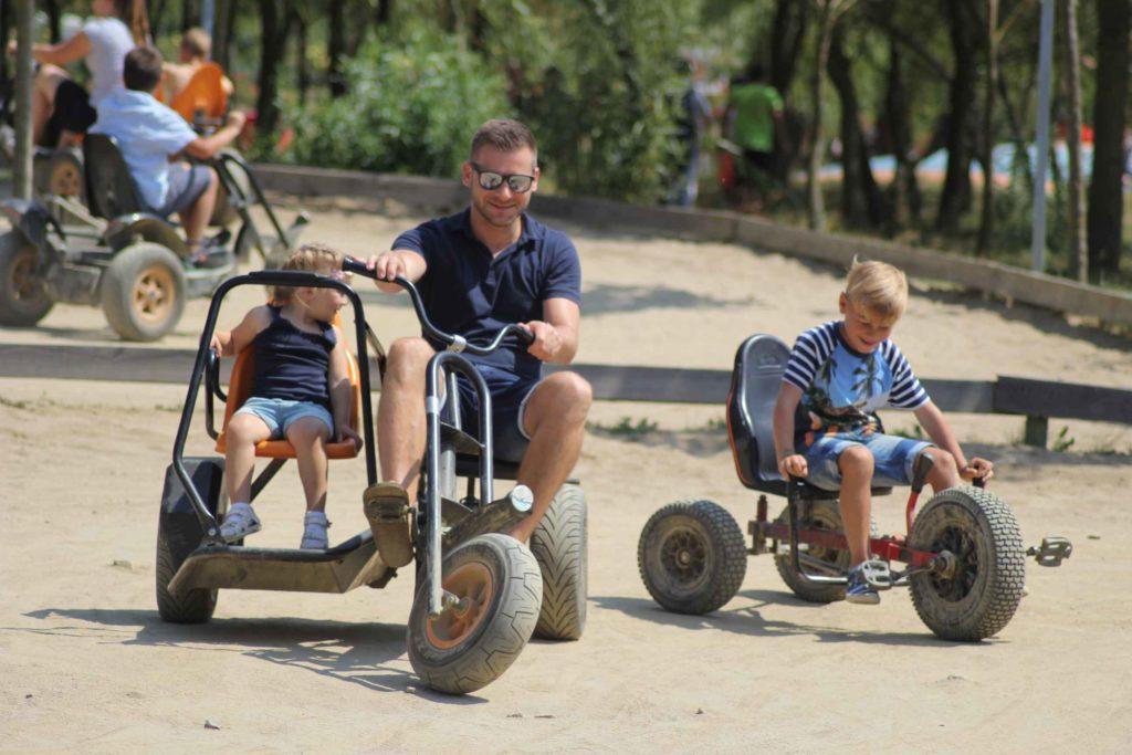 Vater mit Kindern fährt großes dreirad im freizeitpark sonnenlandpark bei lichtenau